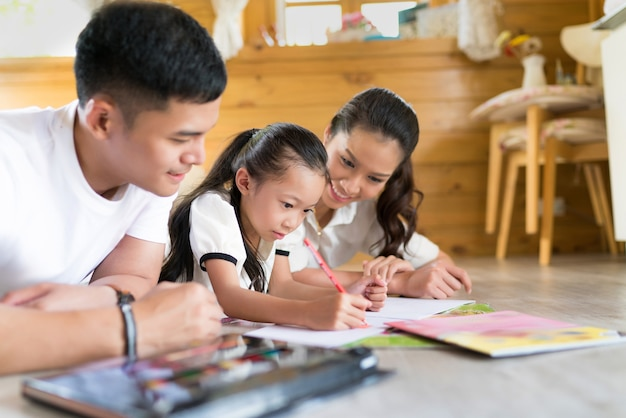 Pai e mãe ensinando as crianças a fazerem o dever de casa em casa