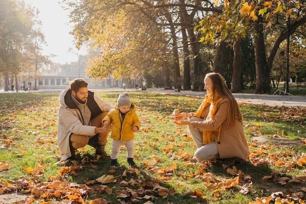 Pai e mãe felizes brincando com o bebê ao ar livre