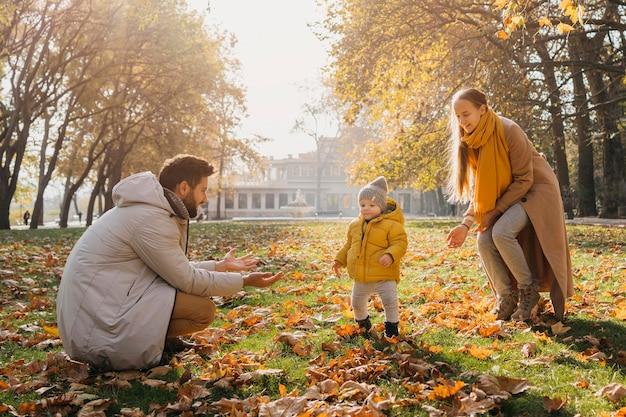 Pai e mãe felizes brincando com o bebê lá fora