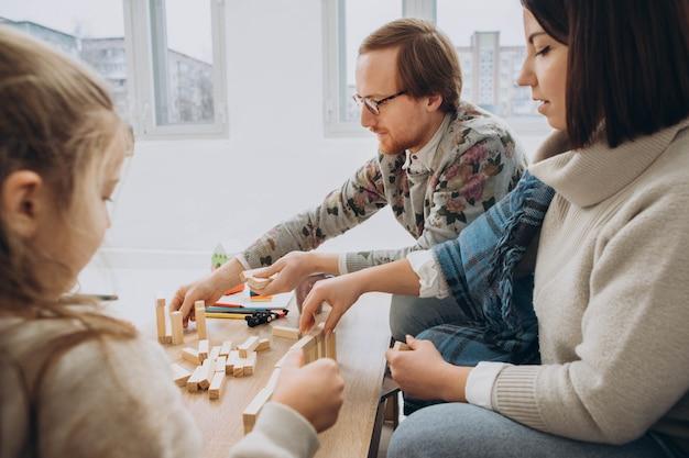 Pai e mãe jovem jogam jogos educativos com crianças