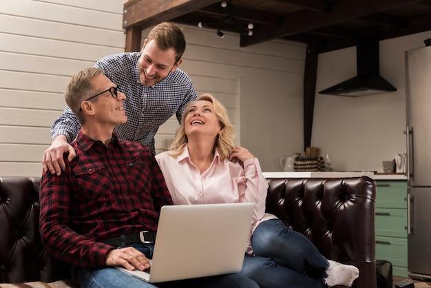 Pai e mãe no sofá com laptop e filho