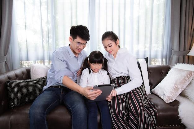 Pai e mãe que ensinam os filhos usam o tablet para fazer os deveres de casa em casa. família asiática está feliz