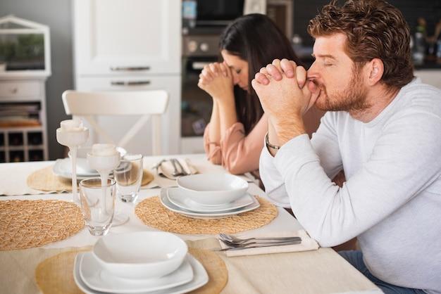 Pai e mãe rezando juntos em casa