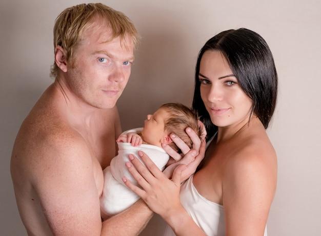 Pai e mãe segurando o bebê dormindo juntos
