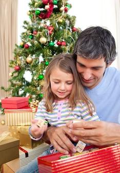 Pai e menina brincando com presentes de natal