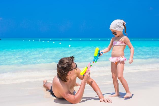 Pai e menina na praia tropical se divertindo