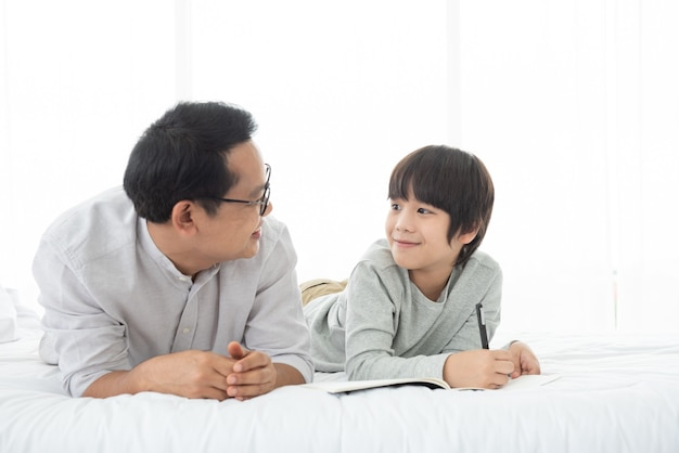Pai e menino asiático escrevendo no livro, deitado na cama em casa, pai e filho passando bons momentos juntos.