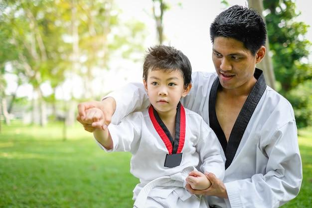 Pai é professor ensinando taekwondo crianças, crianças menino estão aprendendo na natureza