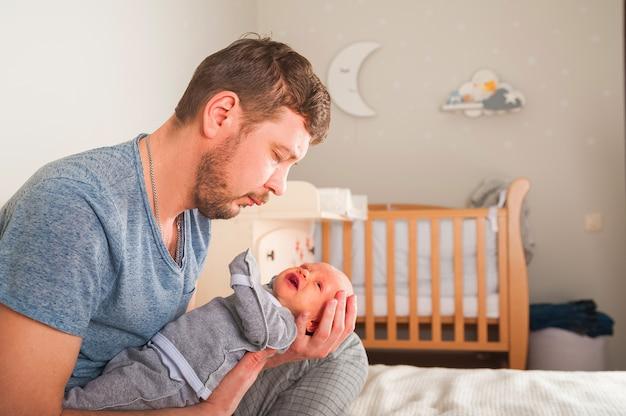 Pai e recém-nascido no interior do quarto de scandi. o pai canta uma canção de ninar para a criança. pai acalma o bebê antes de ir para a cama em seus braços.
