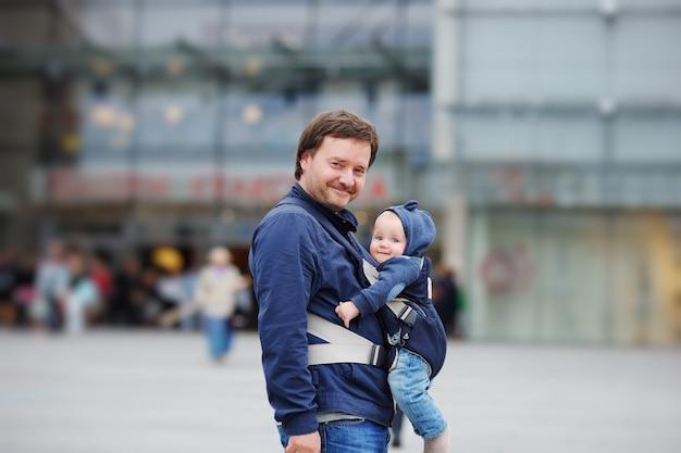 Pai e seu bebê em uma transportadora de bebê na cidade grande