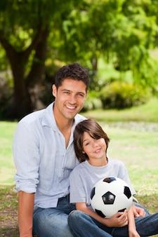 Pai e seu filho com a bola no parque