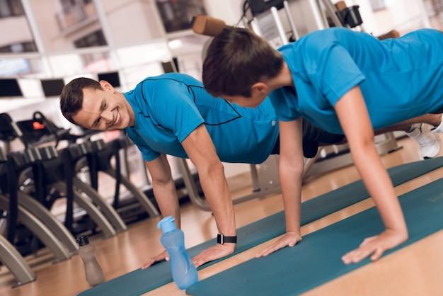 Pai e seu filho fazem flexões no ginásio.