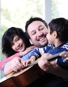 Pai e seus filhos que têm bons momentos em casa