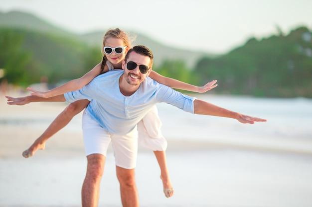 Pai e sua adorável filha pequena na praia