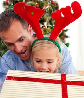 Pai e sua filha que abre presentes de natal