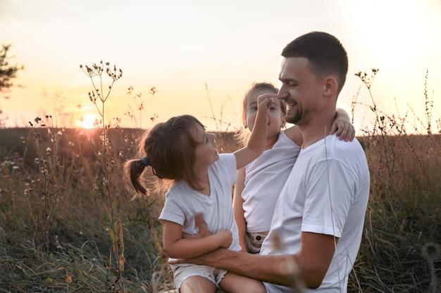 Pai e suas filhas no campo ao pôr do sol.