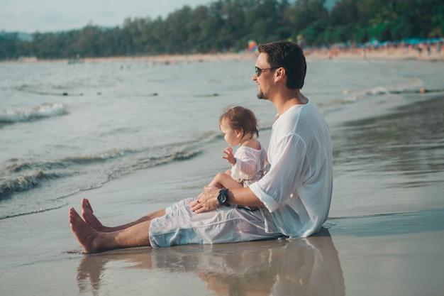 Pai em óculos de sol detém o bebê em seus braços na praia. o conceito de educar o pai de crianças pequenas, infância feliz, uma família amigável.
