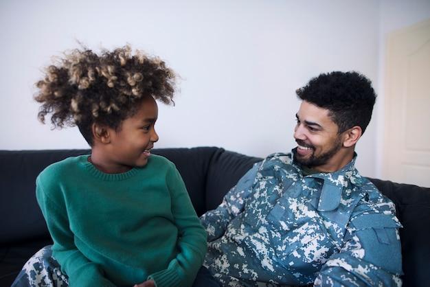 Pai em uniforme militar e filha conversando depois de muito tempo sem ver