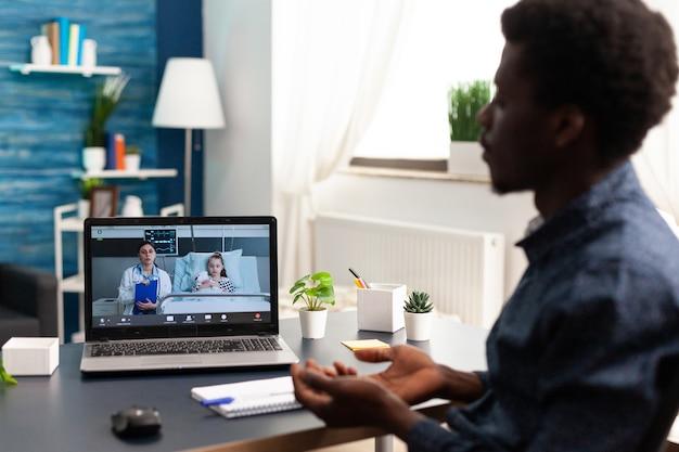 Pai em videochamada online via laptop falando com médico da enfermaria do hospital sobre saúde infantil ...