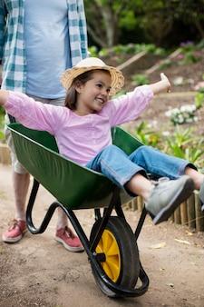 Pai empurrando filha no carrinho de mão
