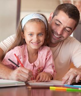 Pai encantado ajudando sua filha a fazer a lição de casa