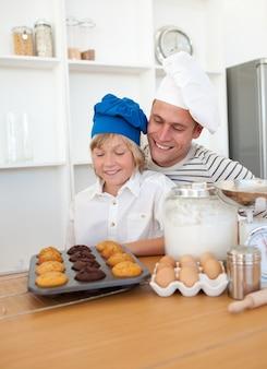 Pai encantador e seu filho apresentando seus muffins