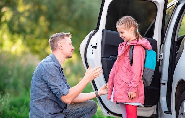 Pai encontrando garotinha depois das aulas no estacionamento