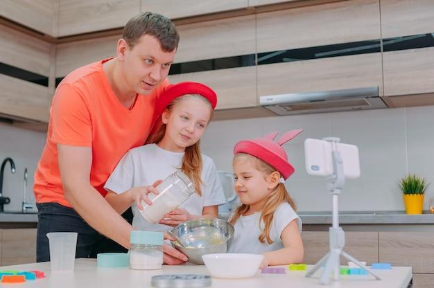 Pai ensina duas filhas a cozinhar massa na cozinha