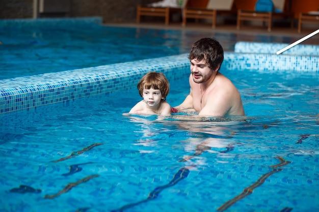 Pai ensina filho a nadar na piscina.