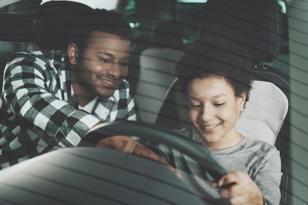 Pai ensina filho pequeno dirigindo a família no carro