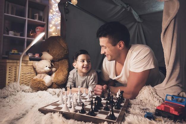 Pai ensina o filho pequeno a jogar xadrez à noite em casa