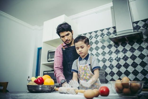 Pai ensina seu filho a cozinhar na cozinha em casa. conceito de família.
