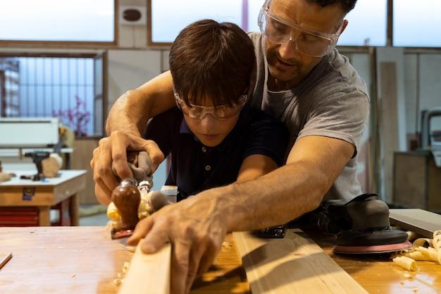 Pai ensinando carpintaria ao filho e lixando madeira.