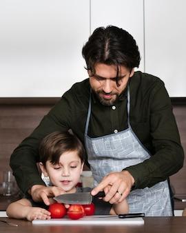 Pai ensinando filho a cortar tomate