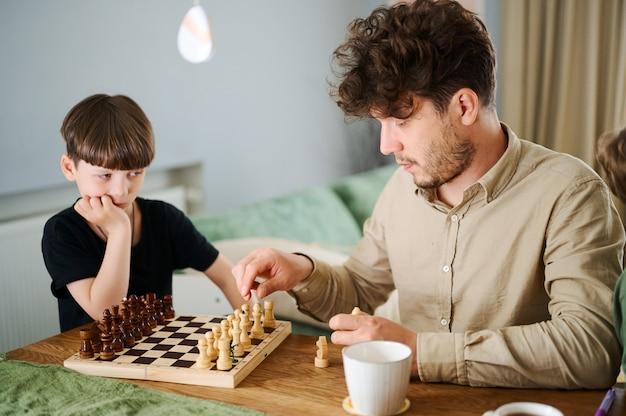 Pai ensinando filho a jogar xadrez conceito de educação e ensino