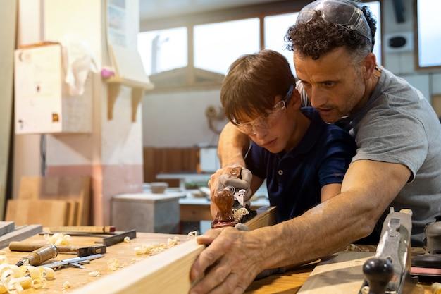Pai ensinando filho a trabalhar com madeira na carpintaria.