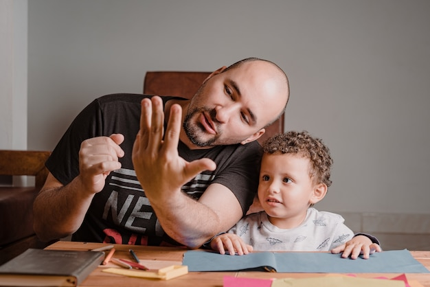 Pai ensinando seu filho a contar números com as mãos