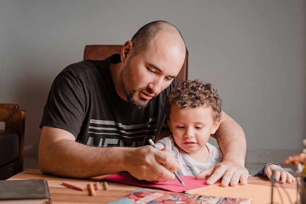 Pai ensinando seu filho a pegar o lápis para desenhar nas folhas coloridas