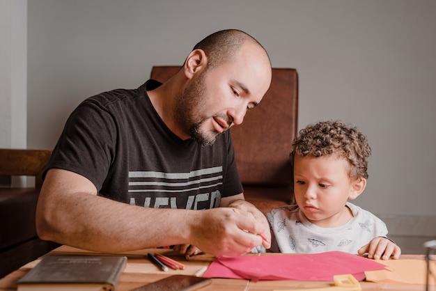Pai ensinando seu filho a pegar o lápis para escrever no bloco
