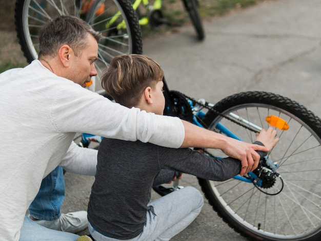 Pai ensinando seu filho consertando a bicicleta por cima do ombro