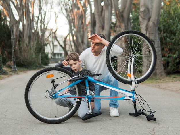 Pai ensinando seu filho e consertando a bicicleta