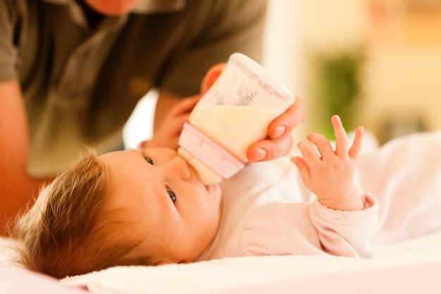 Pai está alimentando seu bebê com uma garrafa; cena muito tranquila
