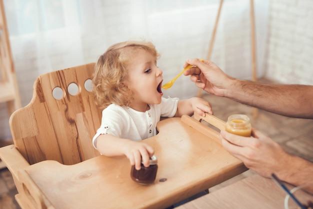 Pai está alimentando seu filho pequeno em casa.