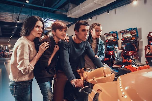 Pai está andando de moto no arcade. família está torcendo.