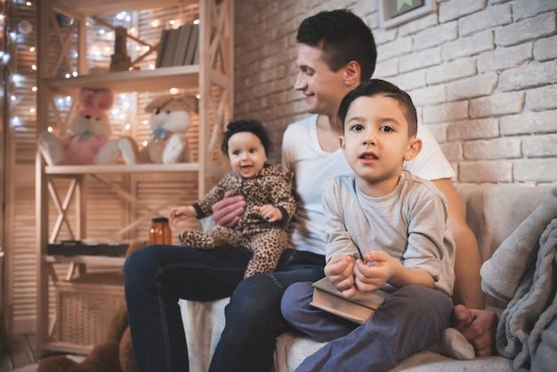 Pai está brincando com filho e filha bebê no sofá