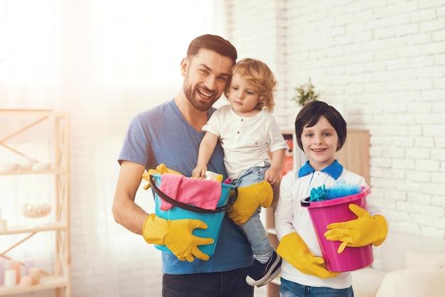 Pai está ensinando aos filhos uma casa de limpeza.
