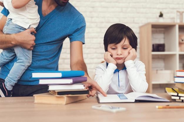 Pai está fazendo um dever de casa com o filho.
