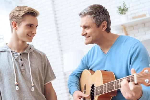 Pai está tocando guitarra com o filho.