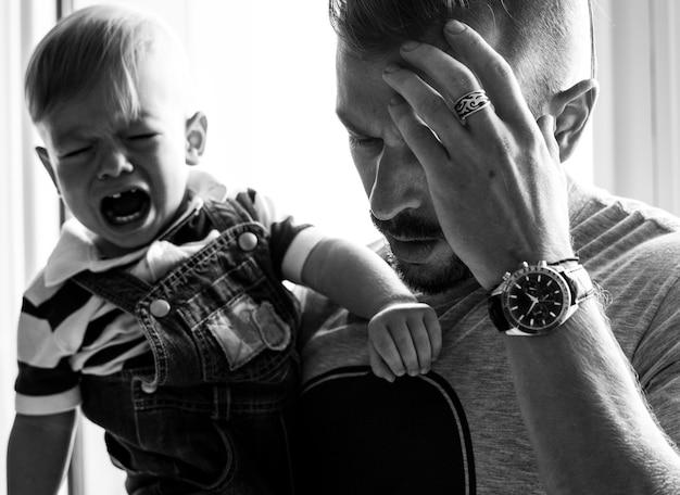 Pai estressado segurando um bebê chorando