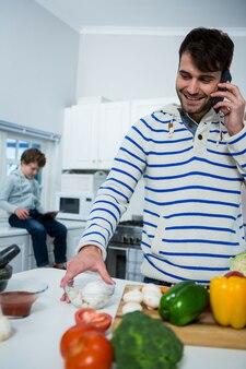 Pai falando no celular enquanto trabalhava na cozinha